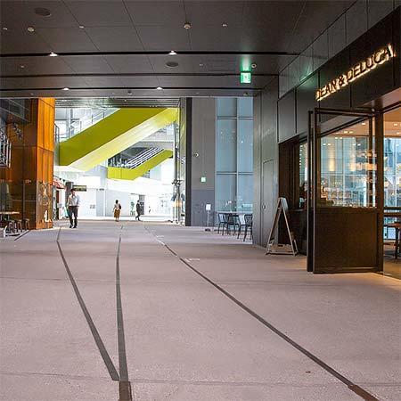 渋谷ストリーム2階.床面には旧東横線の線路跡をイメージしたレールが埋め込まれている.奥が渋谷駅